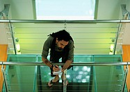 Man leaning on rail, writing, high angle view (thumbnail)