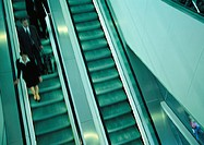 Business people on escalator going down, blurred, high angle view