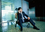 Businessman sitting on luggage cart talking on cell phone