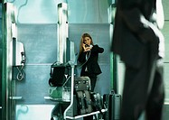 Businesswoman talking on public pay phone in airport