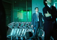 Businessmen standing in front of airport luggage carts