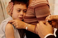 Flu vaccination. Syringe held by a general practice (GP) doctor preparing to inject an influenza (flu) vaccine into the arm of a boy being comforted b...
