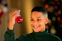 Portrait of a smiling boy holding up a red Christmas ornament.