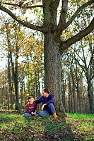 Wide view of a father and son talking while sitting outdoors at the base of a tree.
