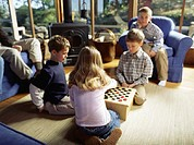 Family Playing Checkers in the Den