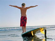boy balancing on surfboard