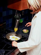 woman frying eggs