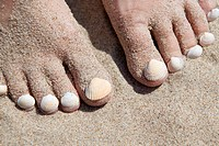 Seashells on woman´s footnails on sandy beach