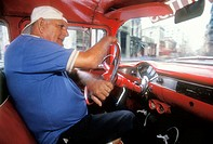 Man driving clssic american car on city streets. Havana. Cuba