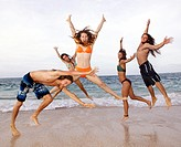 A group of friends jump in the air at the waters edge on the beach