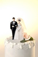 Wedding cake with a miniature bride and groom cake topper and one rose resting on cake next to the bride