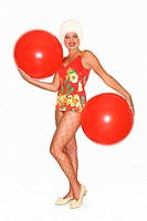 Portrait of a young woman in a retro swimsuit holding two  beach balls