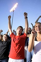 Teens cheering for their team in the stands at a game