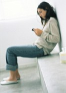 Woman sitting, leaning against wall, side view, blurred