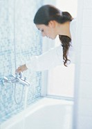 Woman turning bath faucet, blurred