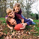 A boy and girl pile on top of their father while playing football in the front yard