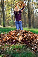 A boy lies covered in a pile of leaves as his sister tosses more on him