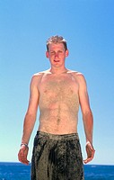 Portrait of 21 year old man wearing bathing suit, covered with sand