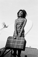 Woman in plaid dress, holding plaid suitcase in front of her