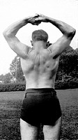 View from back of man in dark color shorts and no shirt with hands together over head, flexing back muscles