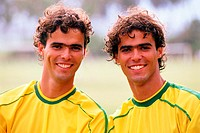 Portrait of two young-adult twin males wearing Brazilian soccer jerseys