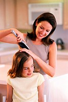 An adult female brushing her daughters hair