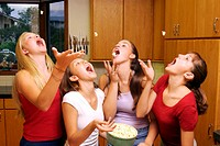 Four teenage girls standing together in a kitchen