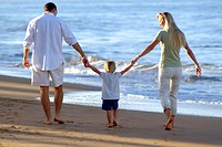 Rear view of a mother, father, and their little girl, holding hands, walking together on the beach