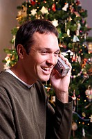 Man in front of Christmas tree with phone