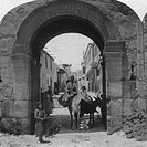 Man riding horseback underneath arched gate of the city of Damascus