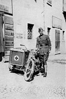 Portrait of a military officer standing next motorcycle with medical supplies