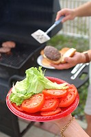 Close-up of a woman holding a plate of tomatoes and lettuce while a man puts a burger on a bun