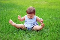 A baby sitting in the grass with her legs in the air