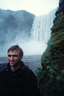 Young man smiling at camera, waterfall behind him