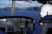 Pilot in a cockpit, ocean and land ahead