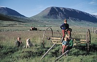 A group of children and a dog sitting on farm equipment