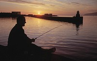 A silhouette of a man fishing by the seaside in the sunset.