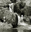 Little boy wearing shorts standing in a creek, small waterfall above, rocks and water