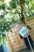 A little boy preparing to swing about in a rope, a treehouse and trees behind