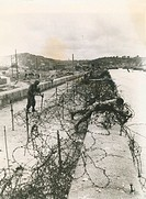 A soldier stands near a barbed wire fence