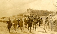 A group of soldiers walk down from a hill