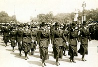 A group of uniformed women march in a parade