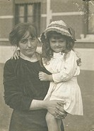 A woman poses holding a girl