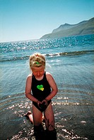A girl in swimsuit kneeling in the ocean, mountainside in backround