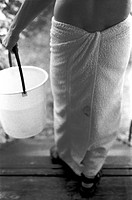 Man in a towel with a bucket in his hand