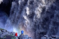 Two people standing on rocks and watching Dettifoss waterfall
