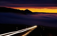 Headlights on a road, fog, mountains and golden sky in distance