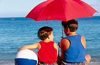Brothers on beach with umbrella