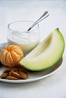 Healthy breakfast. Pot of yoghurt on a plate with a slice of melon (Cucumis melo), a few almonds (Prunus dulcis) and a peeled tangerine (Citrus reticu...