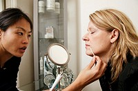 Restylane treatment. Clinician applying local anaesthetic cream around the mouth of a female patient about to undergo Restylane injections. Restylane,...